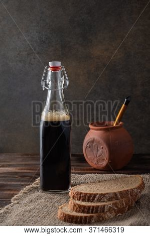 Homemade Tradishional Russian Kvass With Glass Cup And Bread. Behind A Clay Pot With A Wooden Spoon.