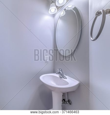 Square Frame Bathroom Interior With Wall Light And Oval Mirror Over Stand Alone Pedestal Sink
