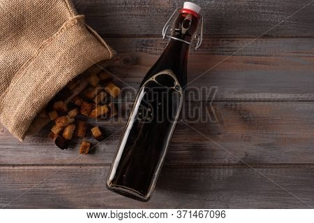 Top View Homemade Tradishional Russian Kvass In Bottle And Crackers In A Bag On Wooden Background. W