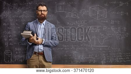 Male teacher holding books in front of a blackboard with math formulas