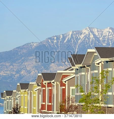 Square Snowy Mountain And Blue Lake View Behind Townhouses With Colorful Exterior Walls