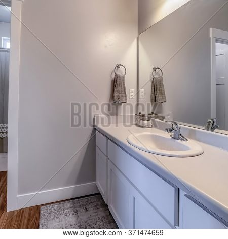 Square Vanity Area Of Bathroom With Door That Leads To The Toilet Bathtub And Shower