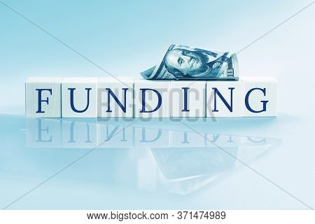 Funding Text On Wooden Blocks On Blue Reflected Background And Us Dollars. Small Business Funding Op