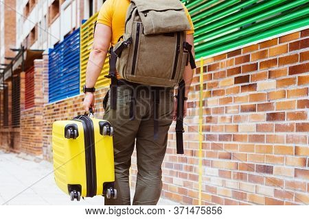 Man Traveling With A Yellow Suitcase And A Backpack