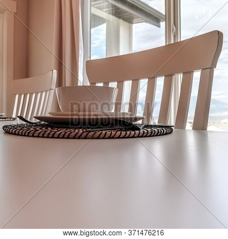 Square Crop Tableware And Utensils On Woven Placemat At The Dining Table With Chairs