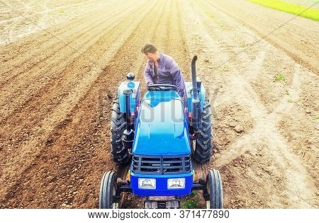 A Farmer On A Tractor Cultivates A Farm Field. Soil Milling, Crumbling And Mixing. Preparatory Work