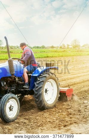 A Farmer On A Tractor Cultivates A Farm Field. Soil Milling, Crumbling And Mixing. Agriculture, Grow