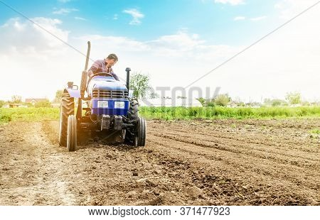 Farmer Is Processing Soil On A Tractor. Soil Milling, Crumbling Mixing. Loosening Surface, Cultivati