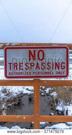 Vertical No Trespassing Signage On A Fence Against Utah Lake And Snowy Shore Background