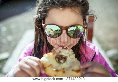 Little Girl Wearing Mirror Sun-glasses And Eating Pizza Outdoors. Closeup