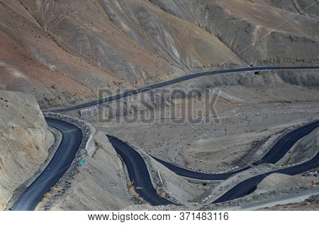 The Black Colour Of A Winding Road Contrast With The Red And Browns Of The Surrounding Mountain Slop