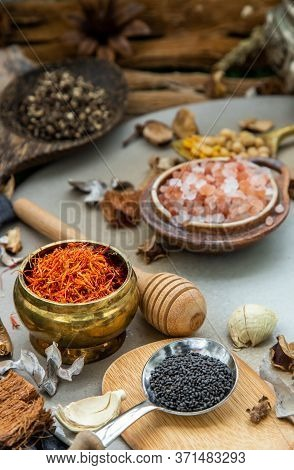 Safflower And Various Spices With Herb In Rustic Style On Balck Background. Natural Herbs Medicine,