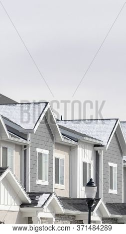 Vertical Facade Of Townhouses In South Jordan Utah With Snowy Gable Roofs In Winter