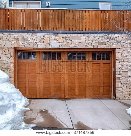 Square Brown Wooden Glass Paned Garage Door Against Stone Wall Under Balcony Of Home