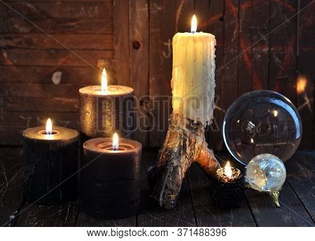 Burning Candles And Magic Crystals On Witch Wooden Table. Esoteric, Wicca And Occult Background With