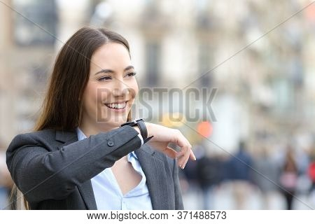 Happy Entrepreneur Woman Dictates Voice Message On Smartwatch Looking Away In The Street