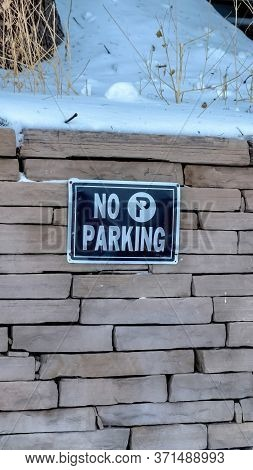 Vertical No Parking Sign On A Stone Brick Retaining Wall Topped With Snow In Winter