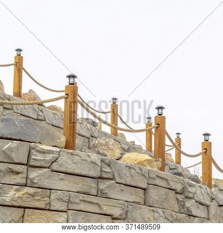 Square Frame Rope Fence With Lamps On Posts Lining A Retaining Wall Made Of Stone Blocks