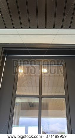Vertical Wooden Front Door Of Home With Glass Panes That Reflects The Outdoor View