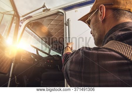 Professional Caucasian Truck Driver In His 40s Getting Into His Truck Cabin. Heavy Duty Transportati