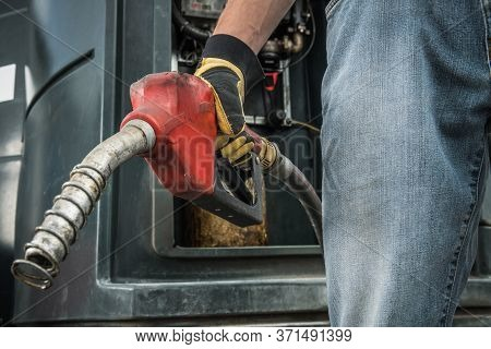 Transportation Industry Theme. Trucker With Diesel Pump Nozzle In His Hand Preparing To Fueling Up H