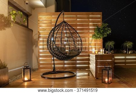 Garden Furniture Design. Starry Night Time In Stylish Backyard Garden With Wooden Porch With Wall An