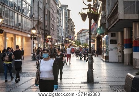 Belgrade, Serbia - May 8, 2020: Old Senior Woman Wearing A Respiratory Face Mask Walking In A Crowde