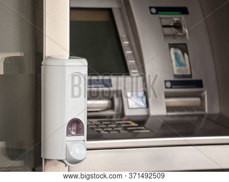 Hand Sanitizer Dispenser Mounted On An Atm Distributing Cash Money In Fron Of A Bank, Full Of Disinf