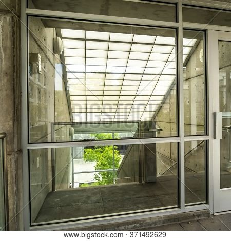 Square Glass Door And Wall With View Of Slanted Frosted Roof Over Stairway Of Building