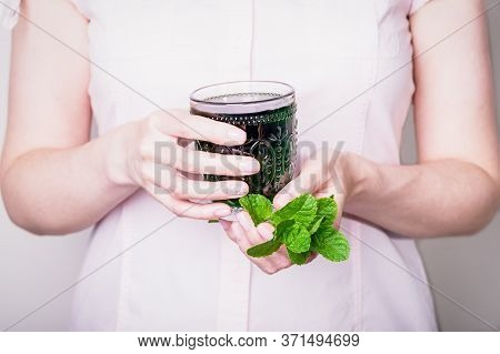 Female Hand Holding Glass Of Green Chlorophyll Drink With Mint Leaves On A Light Pink Background