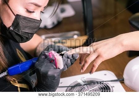 Female Master Uses An Electric Machine To Remove The Nail Polish During Manicure In The Salon. Close