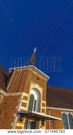 Vertical Frame Facade Of A Church In Provo Utah With Brick Wall Arched Windows And Steeple