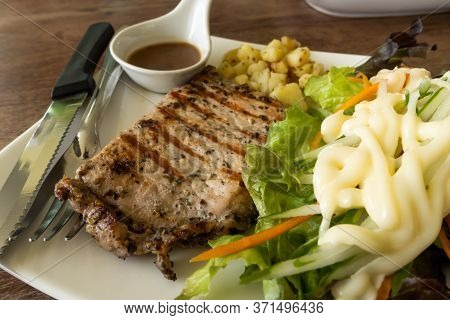 Pork Steak With Black Pepper, Potato And Vegetable In White Plate On Wooden Table.