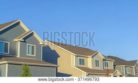 Panorama Frame Homes With Horizontal Wall Sidings And Front Gable Roofs Againts Clear Blue Sky
