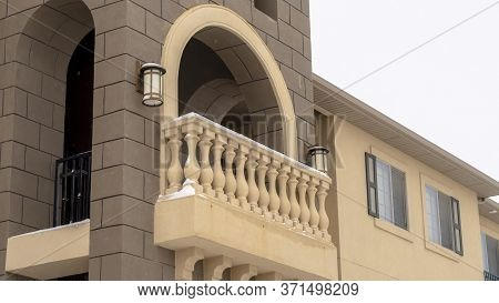 Panorama Exterior Of Apartment With Moulded White Balustrade On The Arched Balcony