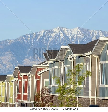 Square Frame Townhouses Exterior With Scenic Lake And Snowy Steep Mountain Background