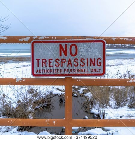 Square Crop No Trespassing Signage On A Fence Against Utah Lake And Snowy Shore Background