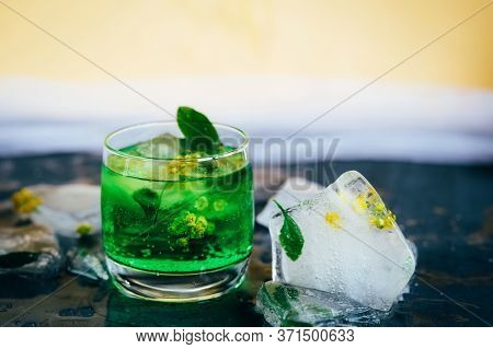 Green Summer Drink Tarhun With Estragon, Ice And Soda, Selective Focus. Frozen Yellow Barberry Flowe