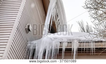 Panorama Roof Of Home With Thick Snow And Sharp Icicles Against Cloudy Winter Sky