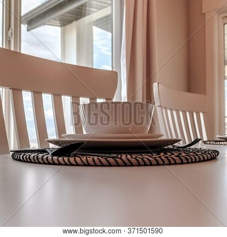 Square Tableware And Utensils On Woven Placemat At The Dining Table With Chairs
