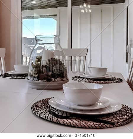 Square Dining Table With Chairs And Tableware Arranged Around A Decorative Centerpiece