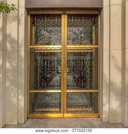 Square Decorative Wrought Iron Door With Gold Frames In Front Of Glass Door Of Building