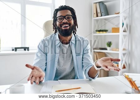 Happy Young African Man In Eyewear Keeping Arms Outstretched And Smiling While Working Indoors