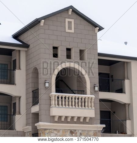 Square Frame Facade Of Apartments With Gabled Arched Balcony At The Center Of The Building