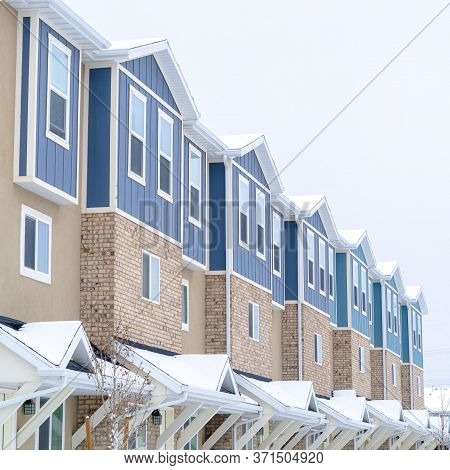 Square Snowy Gable Roofs At The Facade Of Townhome With Brick Wall And Vertical Siding