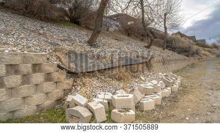 Panorama Conctere Blocks Of A Collapsed Low Retaining Wall Lining A Slope And Dirt Road