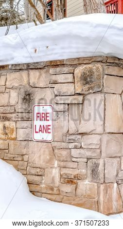 Vertical Crop Stone Retaining Wall With Fire Lane Sign On A Hill With Thick Snow In Winter