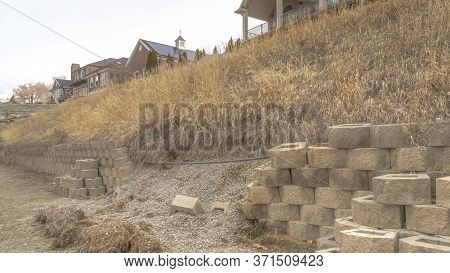 Panorama Damaged Stone Blocks Retaining Wall Lining A Hill With Homes Under Cloudy Sky