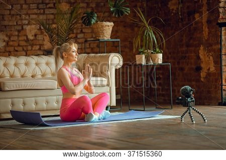 Girl Seating On Yoga Mat In Sport Outfit With Laptop