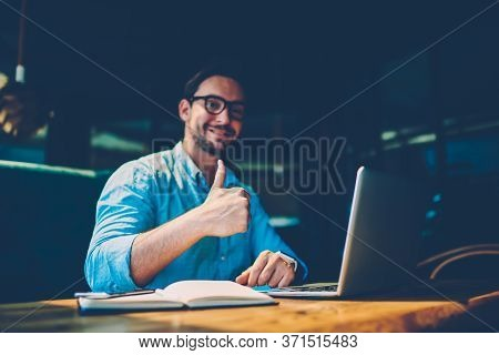 Portrait Of Skilled Male Freelancer Showing Ok Sign Completing Working On Project